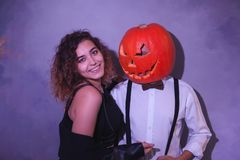Unusual couple at Halloween party, Woman with pumpkin on head royalty free stock photo