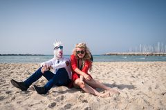 Unusual couple sits on the beach on the background of sea and sky Stock Image