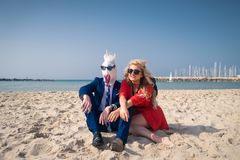 Unusual couple are sunbathing on the beach and enjoys vacation. Comical men in elegant suit and funny mask with women in bright red dress Stock Photos