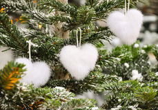 Unusual creative romantic Christmas or New Year decoration -white fluffy heart shape christmas toys on spruce in winter. Stock Image