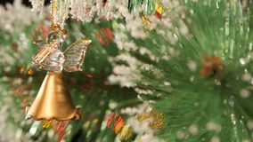 Unusual decoration like angel - a gold toy on. Unusual christmas decoration - a shiny gold toy like angel on christmas tree, bokeh, light, on black background stock footage