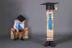 Unusual education concept with a dozing boy student. In mortarboard royalty free stock photography