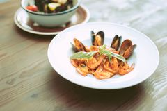 Unusual expensive meals with seafood and sauce standing on wooden table. Pasta with seafood. Unusual expensive meals with seafood and sauce standing on wooden royalty free stock image