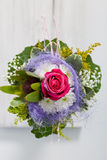 Unusual floral posy incorporating a blue textile. With twirling loose fibres and a central red rose viewed from above on white painted wooden boards royalty free stock photo