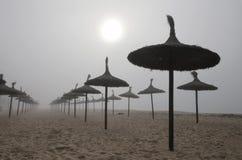 Unusual Fog in el arenal beach in mallorca. Rare and unusual heavy fog over the coast with sun umbrellas of El Arenal beach touristic area during winter in the Stock Photo