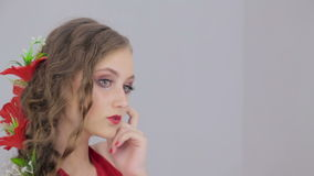 Unusual girl with creative make-up in dress looking at her reflection in mirror. Unusual and mysterious girl with creative make-up and elegant hairstyle with stock video footage