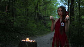 Unusual girl with creative make-up holding two burning candles in dark forest. Unusual and mysterious girl with creative make-up and elegant hairstyle in ethnic stock video footage