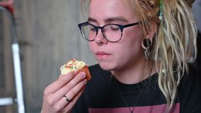 An unusual girl with dreadlocks on her head and a piercing eats a cupcake in a cafe. A young woman in glasses is having. Breakfast with a cupcake against a gray stock footage
