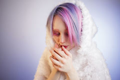 Unusual girl with pink hair, feel cold in fur. A young girl with pink eyes and hair, like a doll royalty free stock images
