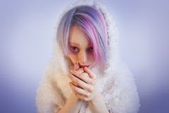Unusual girl with pink hair, feel cold in fur. A young girl with pink eyes and hair, like a doll stock image