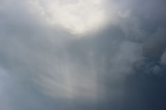 Unusual glow of sunlight through dark gray rain clouds before a thunderstorm in the summer. Royalty Free Stock Photo