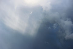 Unusual glow of sunlight through dark gray rain clouds before a thunderstorm in the summer. Stock Photos
