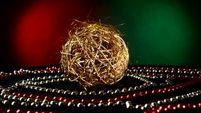 Unusual gold toy for Christmas or New Year and. Unusual shiny gold toy for Christmas tree for decoration Christmas or New Year and red and white beads, rotation stock footage