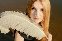 Unusual gothic girl with long red hair and feather Royalty Free Stock Photography