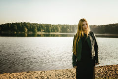 Unusual Gothic girl with long red hair reflects at lake Stock Photo