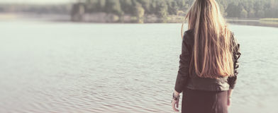 Unusual Gothic girl with long red hair reflects at lake Stock Images