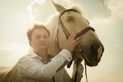 Unusual groom at wedding on white horse outdoors Stock Images