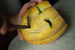 Unusual Halloween melon, cutting process, knife and male hands Royalty Free Stock Image