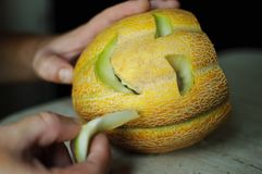 Unusual Halloween melon, cutting process, knife and male hands Royalty Free Stock Photography