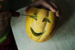 Unusual Halloween melon, cutting process, knife and male hands Stock Images
