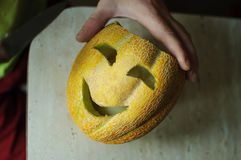 Unusual Halloween melon, cutting process, knife and male hands Stock Photos