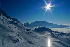 Unusual halo light effect, the sun reflects off the snow and creates a bright pillar of light high in the mountains stock images
