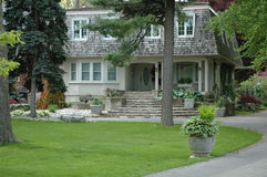 Unusual House. Unusual elegant stucco house with concret flower urn / planter along driveway stock photos
