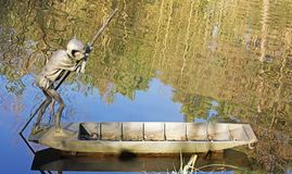 Statue of a Goblin punting on a Lake royalty free stock photography