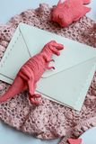 Unusual letter in envelope and toy dinosaur in trendy colors on crocheted napkin, living coral background
