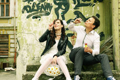 Unusual loving wedding couple near wall with graffiti thrown hou Stock Images