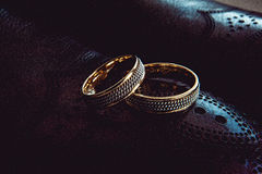 Unusual luxery wedding rings. On the dark perforated leather of a shue Royalty Free Stock Photo