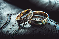 Unusual luxery wedding rings. macro. Unusual luxery wedding rings on the dark perforated leather of a shue Stock Photos