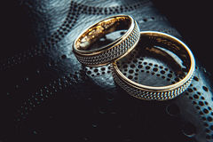 Unusual luxery wedding rings. macro. Unusual luxery wedding rings on the dark perforated leather of a shue Royalty Free Stock Images