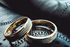 Unusual luxery wedding rings. macro. Unusual luxery wedding rings on the dark perforated leather of a shue Stock Photography