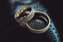 Unusual luxery wedding rings. macro. Unusual luxery wedding rings on the dark perforated leather of a shue Royalty Free Stock Photos