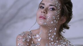 Unusual makeup and face art with sparkling rhinestones on the skin.