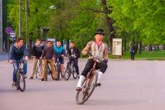 Unusual man rides on retro bike in Vilnius stock photos
