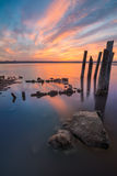 Unusual pillars in the water on the background of colorful sky Royalty Free Stock Photography