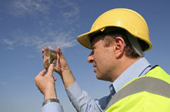Unusual plant specimen. An environmental engineer, wearing protective clothing, with an unusual plant specimen in a glass beaker with a great blue sky behind him royalty free stock photography