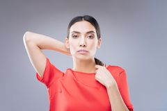 Curious young woman being interested in changing her haircut. Unusual ponytail. Pleasant beautiful woman being tired of her usual hairstyle and trying something royalty free stock photo