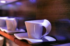 Unusual porcelain white cups and saucers displayed on a wooden shelf. stock photos