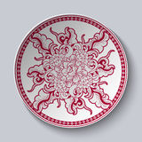 Unusual red and white floral pattern applied to decorative ceramic plate with a red border. Dish is isolated on white background. Royalty Free Stock Image