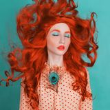Unusual redhead girl with long curly hair on blue background. Beauty portrait. Hair coloring in salon. Redhead model in yellow