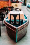 Unusual restaurant interior: dining table in the colorful fish boat. Marine ambience.  Stock Image