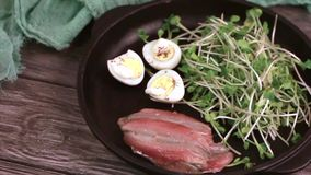 Unusual salad with leek sprouts, quail eggs and anchovies served in cast-iron pan stock video footage