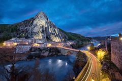 Unusual shaped rock at dusk in Sisteron, France. Sisteron in the evening: The Rocher de la Baume - peculiar shaped rock and bridge over Durance river, Alpes-de Royalty Free Stock Photos