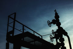 Unusual silhouette of gas rig drill, on the background of blue a Stock Images