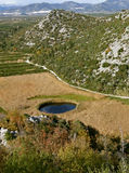 Unusual, small lake in the shape of the eye. Croatia abounds with natural beauty. This is one of them. Lake in the shape of the eye in the middle of a field Stock Photography