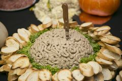 An unusual snack on a large plate, in the center of which is a mountain of pate in the form of brains with a stabbed knife, and ar royalty free stock images