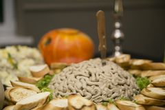 An unusual snack on a large plate, in the center of which is a mountain of pate in the form of brains with a stabbed knife, and ar royalty free stock image